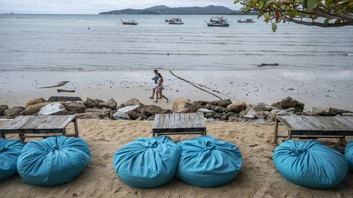 People are seen strolling by the sea from a beach bar in Phuket, Thailand