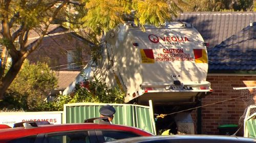 A garbage truck has smashed through a garden in Belrose, Sydney.