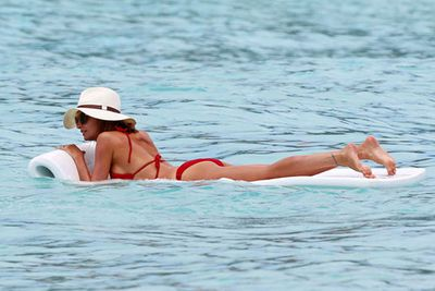 Sun-safe Nic knows how it's done. The fashion star chills out in a red bikini, shades and chic floppy hat whilst on holidays with pal Jessica Alba.