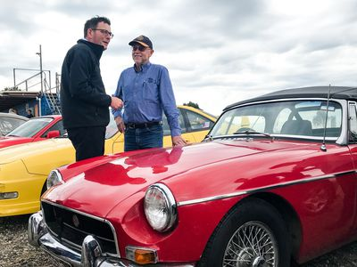 The premier admires a very flashy red car after promising a $5 million investment for motor sports upgrades.