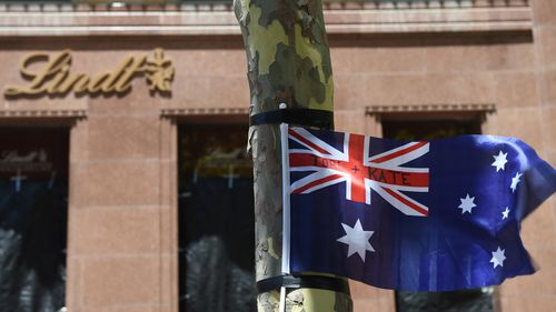 A flag blows in the wind, bearing the names of siege victims Tori Johnson and Katrina Dawson. (AAP)