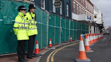 Police officers stand watch near where a Russian double agent and his daughter were poisoned. (AAP)