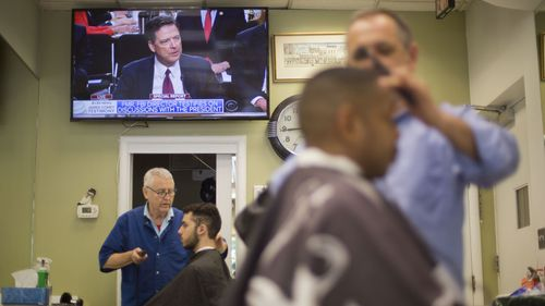 Barbers at Puglisi Hair Cuts in Washington tend to customers as televised coverage of former FBI director James Comey testifying plays out on June 8, 2017. Photo: AP