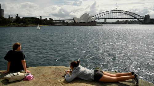 Tourists lie in the sun in Sydney Harbour.