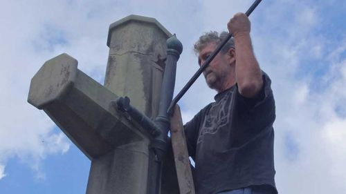 Men charged after removing sword from cross at war memorial
