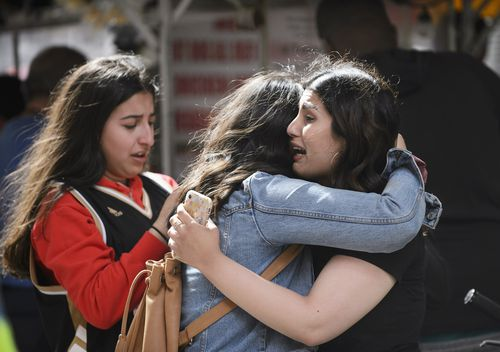 Friends embrace after shots were fired during the Toronto Raptors NBA basketball championship parade (Andrew Lahodynskyj/The Canadian Press via AP)