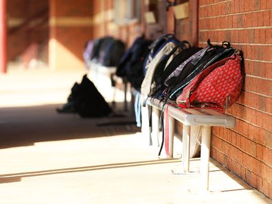 School bags lined up outside classroom.