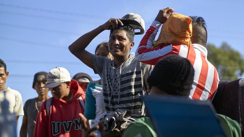 Migrants from Central America line up to begin the process of returning to their countries with the help of the International Organization of Migration outside a shelter set up for members of the migrant caravan on November 26 in Tijuana, Mexico.