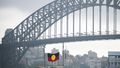 A boat flying the Aboriginal under the Sydney Harbour Bridge on January 26, 2020.