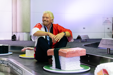 Sir Richard Branson lives out a childhood dream, riding the baggage belt.