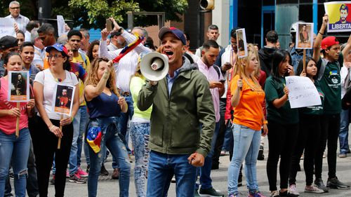 """Opposition politician Gilbert Caro shouts """"Free elections"""" in a walk out against President Nicolas Maduro, in Caracas, Venezuela."""