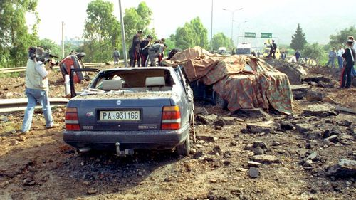 A file photograph from May 23, 1992, shows the damage at a highway that links Palermo to its airport after a bomb blast killed anti-Mafia prosecutor Giovanni Falcone, his wife and three policemen escorting them. (AAP)