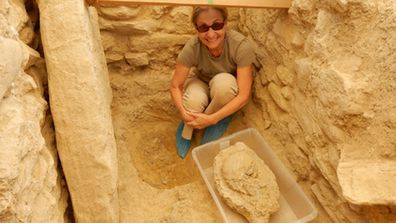 "<p>Archaeologists have&nbsp;literally&nbsp;struck gold&nbsp;after an excavated&nbsp;site in southwest Greece&nbsp;they took to be&nbsp;an ancient house in fact&nbsp;proved to be the tomb of a Bronze Age warrior.</p><p>An international group of researchers, led by archaeologists from the University of Cincinnati stumbled upon a treasure-lined tomb while excavating an unexplored field&nbsp;in Pylos, on the&nbsp;southwest coast of Greece.</p><p>The tomb belongs to an adult male buried about 3500 years ago, dubbed&nbsp;the 'griffin warrior' for an ivory griffon plaque found resting between his legs.</p><p>More than 1400 artefacts including a&nbsp;gold-and-ivory hilted&nbsp;sword, gold necklaces, rings and precious stone beads have been recovered from the site – one of the biggest hauls&nbsp;at any single burial site in Greece ever.</p><p>The find has been hailed by&nbsp;a university representative as&nbsp;""one of the most magnificent displays of prehistoric wealth discovered in mainland Greece"" in more than six decades.</p><p>Here, senior research associate Sharon Stocker  poses with a 3500 year-old skull found in the ancient tomb. </p><p><strong>Click through the gallery to see video and images of the surprise treasures.</strong></p><p>(University of Cincinnati)</p>"