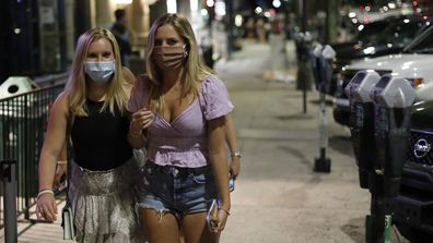 Women in masks walk along College Avenue in downtown Athens, Georgia, USA last month after The Athens-Clarke Commission approved a mandate on wearing masks when in public places and inside commercial establishments.