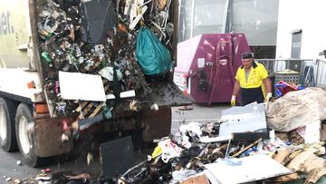 Council workers help search through garbage to try and find a pink garbage bag with precious weddings inside.