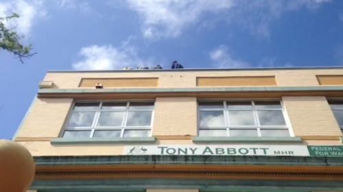 The four protesters are sitting at the edge of the roof. (Grant Williams, ACA)