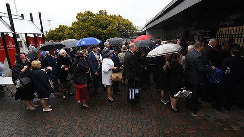 Racegoers line up in the rain outside Flemington Racecourse. (AAP)