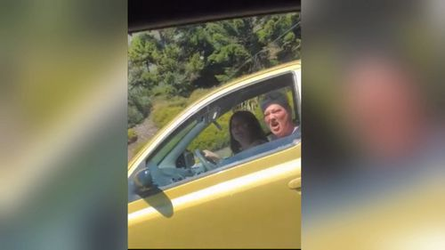 Two woman seen hurling abuse and objects at another car.
