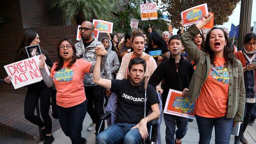 Cristina Jiminez, left, and Ady Barkan, in wheelchair, lead a small delegation urging the Democrats to protect the Deferred Action for Childhood Arrivals (DACA) program in Los Angeles. (AAP)