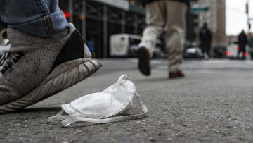 A used protective face mask rests on the pavement as pedestrians pass, Tuesday, March 17, 2020, in New York.