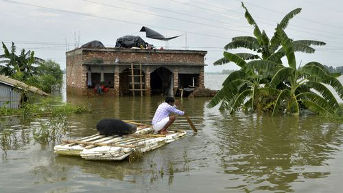 An Indian villager uses a banana raft outside his partially flooded house. (AFP)