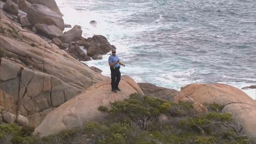 An officer scours the waters off Mermaid Beach in search for the missing fisherman.