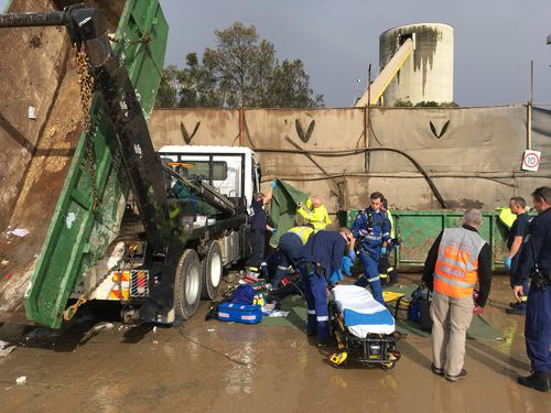 A man, aged in his 50s was freed after getting trapped by a garbage truck at a worksite in Sydney's west this morning.