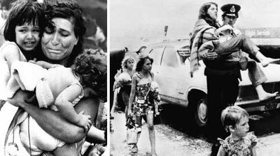 In one of the most iconic photos of Cyclone Tracy, Mariana Gatis holds her children in her arms. Right: A policeman carries an injured girl into the air terminal on December 27, 1974 at Darwin airport. (AAP)