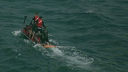 Lifeguards on jetskis are searching for the shark. (9NEWS)