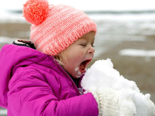 A little girl gets her first taste of snow. (Image: AAP)