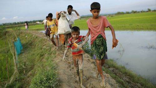 Rohingya refugees walk in a muddy road as they enter Bangladesh border in Teknaf, Bangladesh, 10 September 2017. (AAP)