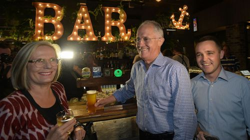 Prime Minister Malcolm Turnbull, his wife Lucy and Assistant Minister for Innovation Wyatt Roy have a drink at a Politics in the Pub event in Sandstone Point. (AAP/Lukas Coch)