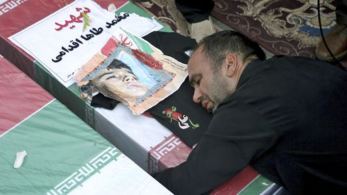 Father of Mohammad Taha Eghadami, a 4-year-old boy who was killed in Saturday's terror attack on a military parade, mourns over his coffin during a mass funeral ceremony for the victims.
