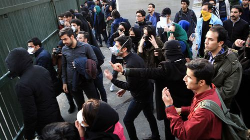 Iranian students clash with riot police during an anti-government protest around the University of Tehran, Iran. (AAP)