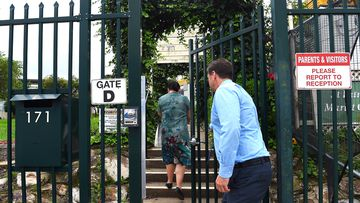 The deputy principal of St Patrick's Marist College in Dundas, Sydney opens the gate to a parent of a student