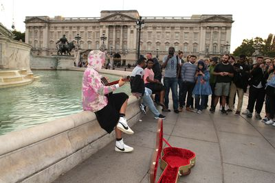 Fans gathered around Bieber who sat on the Victoria Monument outside Buckingham Palace to play his guitar.