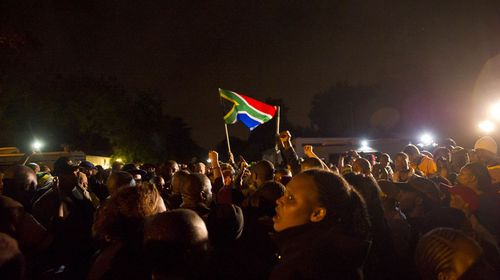 A South African flag soars through the darkness as mourners chant and sing in memory of Nelson Mandela's extraordinary life. (Getty)