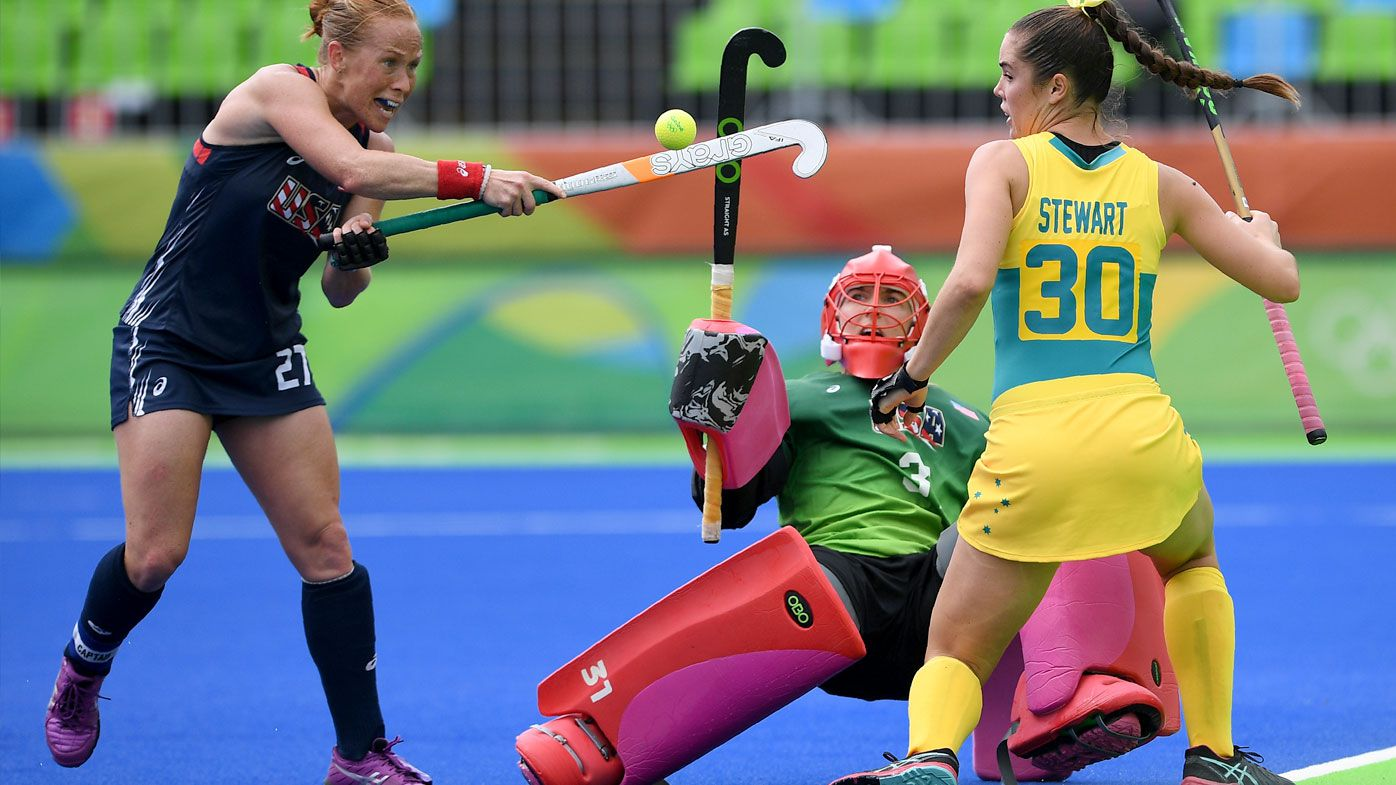 The USA's Lauren Crandall hits the ball as Australia's Gabi Nance and Grace Stewart look on during the women's field hockey Australia vs USA match. (AFP)