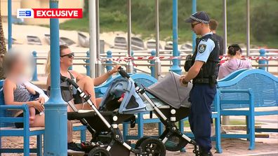 A young mother breastfeeding is spoken to by police.