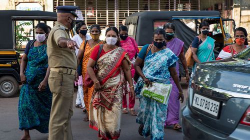 India has recorded more than 70,000 coronavirus cases in a single day.  Pictured are workers leaving the area after the Cochin Special Economic Zone that houses several industrial units was closed as part of COVID-19 containment measures in Kochi, Kerala, India.