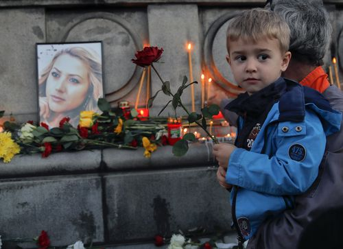 A child holds next to a portrait of slain television reporter Viktoria Marinova during a vigil at the Liberty Monument in Ruse, Bulgaria
