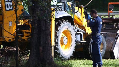 Police take photographs as an excavator works to dig up the backyard. (9NEWS)