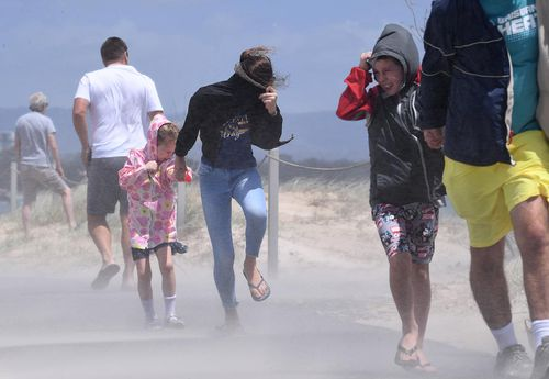 People struggle with blowing sand and high winds on the Gold Coast.