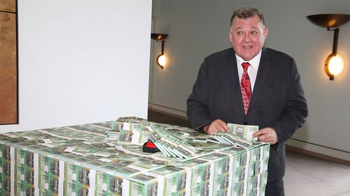 Independent MP Craig Kelly holding a fake 'trillion-dollar' note.