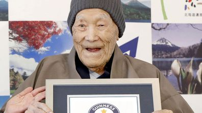 Masazou Nonaka receives the certificate from Guinness World Records as the world's oldest living man at age 112 years and 259 days during a ceremony in Ashoro on Japan's northern main island of Hokkaido. (AAP)