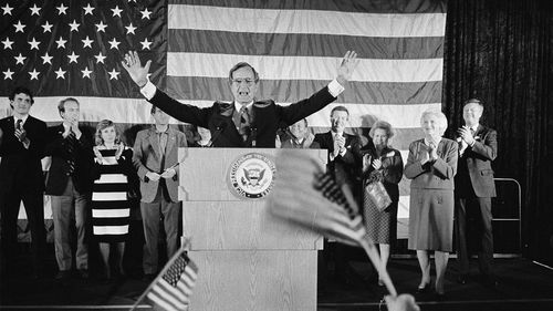 Flag-wavers greet Vice President George Bush after he was re-elected to the post of vice president, in Houston, Texas in 1984. Bush has died at age 94.