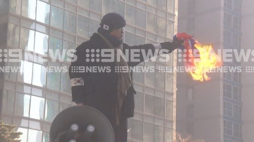 A North Korean flag is burnt in the protests. (9NEWS)