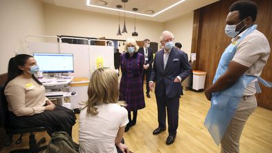 Britain's Prince Charles and Camilla, Duchess of Cornwall talk with staff during a visit to the Queen Elizabeth Hospital in Birmingham, England, Wednesday Feb. 17, 2021, to thank volunteers undertaking clinical trials for the COVID-19 vaccinations.
