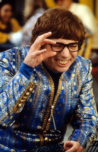 Mike Myers wearing an ornate blue jacket while squinting through his black rimmed glasses in a scene from the film 'Austin Powers: The Spy Who Shagged Me', 1999.