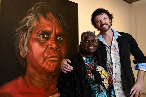 Aboriginal Elder Daisy Tjuparntarri Ward and artist David Darcy pose for a photograph in front of David's portrait of Daisy.
